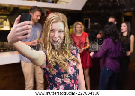 Pretty blonde taking a selfie at the bar - stock photo