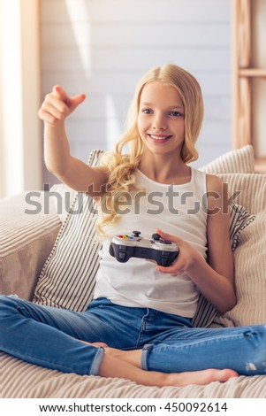 Pretty blonde teenage girl is playing game console, pointing and smiling while sitting on sofa at home - stock photo