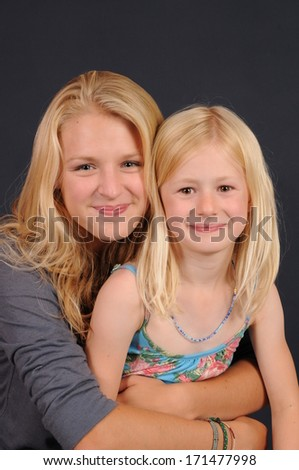 pretty blonde teenage girl with younger girl isolated on dark background - stock photo