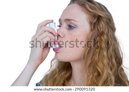 Pretty blonde using an asthma inhaler - stock photo