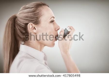 Pretty blonde using an asthma inhaler against blue vignette background - stock photo