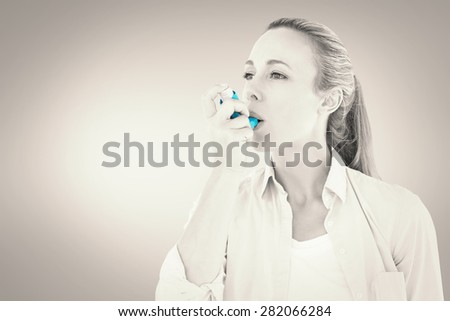 Pretty blonde using an asthma inhaler against grey vignette - stock photo