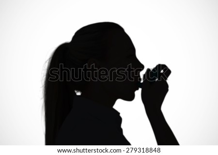 Pretty blonde using an asthma inhaler against white background with vignette
