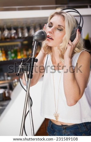 Pretty blonde with headphone singing into microphone at the nightclub - stock photo