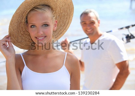 pretty blonde with sun hat and boyfriend in background - stock photo