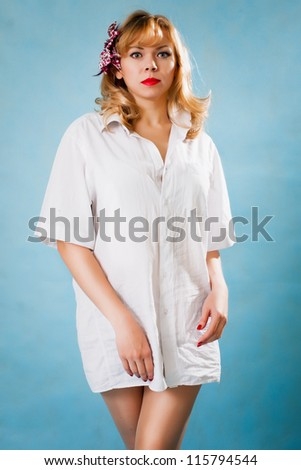 Pretty blonde with  white shirt in pinup style on blue background - stock photo