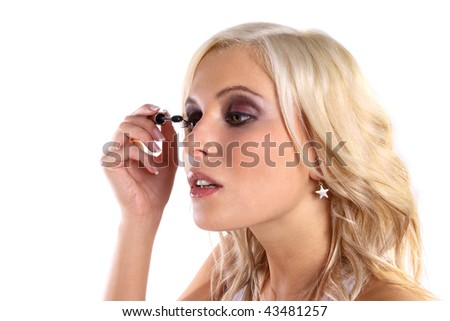 Pretty blonde woman applying makeup on eyelash
