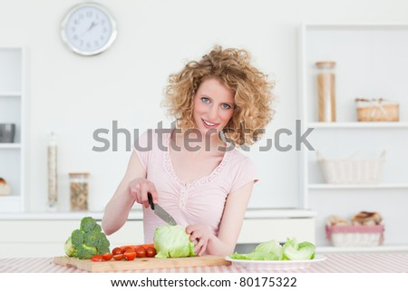 Pretty blonde woman cooking some vegetables in the kitchen in her apartment - stock photo