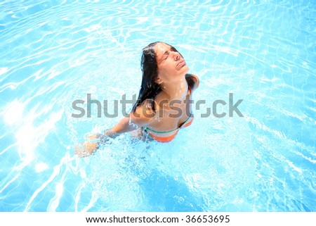 Pretty blonde woman enjoying a swimming pool in Greece