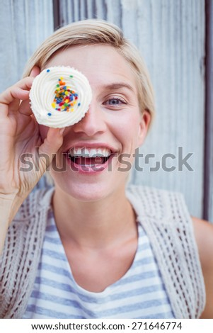 Pretty blonde woman grimacing with cupcake on wooden background - stock photo