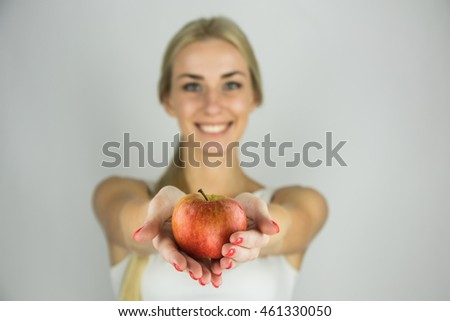 Pretty blonde woman hold an fresh red apple. Conception of vegetarian or healthy food
