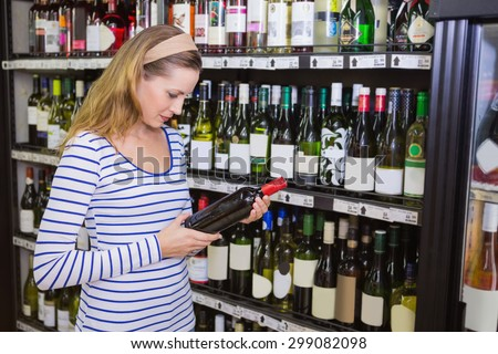 Pretty blonde woman holding a bottle of red wine at supermarket - stock photo
