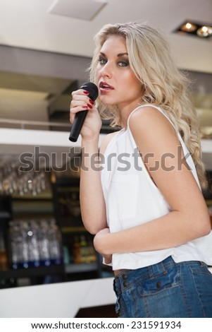 Pretty blonde woman holding a micro while singing at the nightclub - stock photo