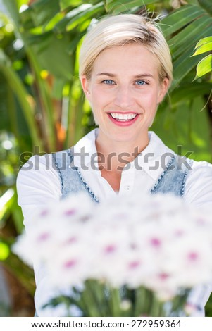 Pretty blonde woman holding bunch of flowers in the park - stock photo