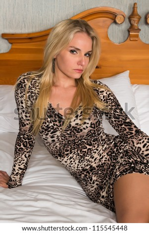 Pretty blonde woman in a leopard print dress - stock photo