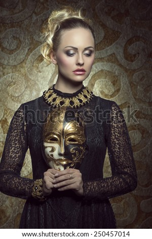 pretty blonde woman in carnival portrait posing with elegant gothic lace dress, baroque jewellery and gold mask. Mysterious masquerade portrait  - stock photo