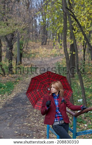 Pretty blonde woman in jeans and jacket standing on the bridge in autumn park and holding an open umbrella - stock photo