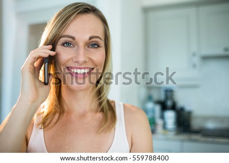 Pretty blonde woman on the phone at home