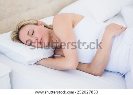Pretty blonde woman sleeping in bed at home in the living room - stock photo