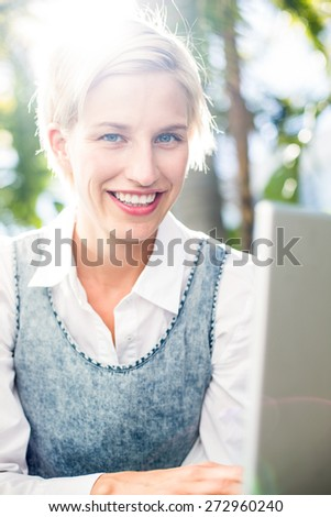 Pretty blonde woman using her laptop in the park - stock photo