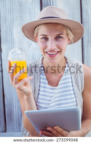 Pretty blonde woman using her tablet and holding orange juice on wooden background - stock photo