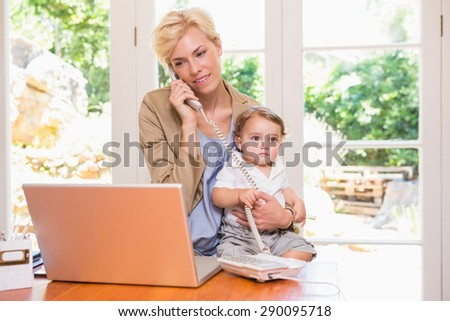 Pretty blonde woman with his son phoning and using laptop in the office - stock photo