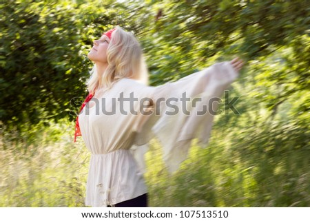 Pretty blonde woman with outstretched arms dancing in the summer. Outdoor shot with motion blur against a fresh green background. - stock photo