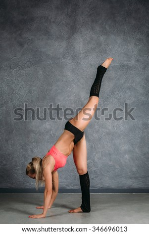 Pretty blonde woman with slim body stand in yoga pose. Gymnastic pose vertical.
