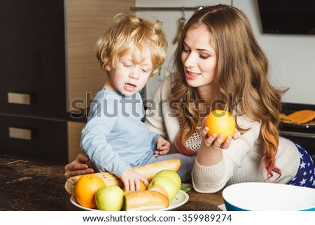Pretty blonde young woman and her little son together in a kitchen