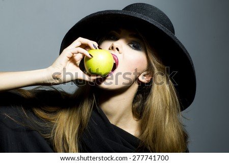 Pretty blonde young woman in retro black hat with bright make up biting fresh green apple standing on gray background copyspace, horizontal picture - stock photo