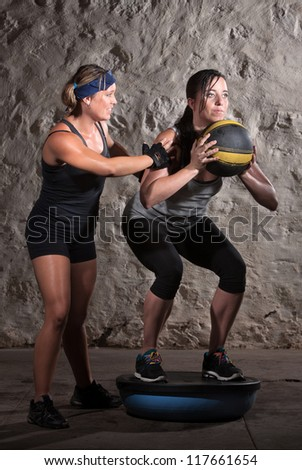 Pretty boot camp fitness instructor with lady on balancing object - stock photo