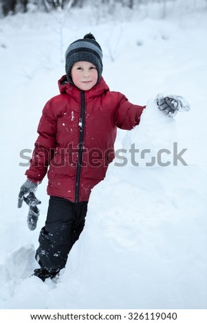 Pretty boy making snowman while playing on snow field - stock photo