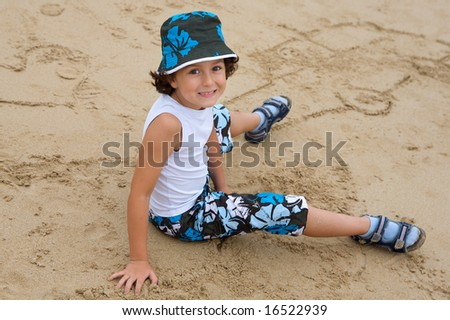 Pretty boy sitting on the sand from the beach in summer