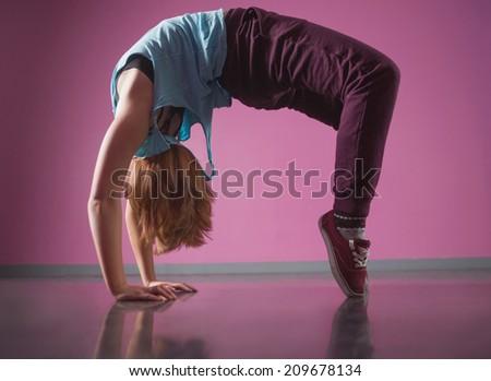 Pretty break dancer doing a back bend in the dance studio - stock photo