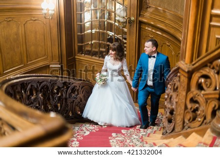 Pretty bride and handsome groom looking towards walking up old wooden stairs on the background of luxury interior