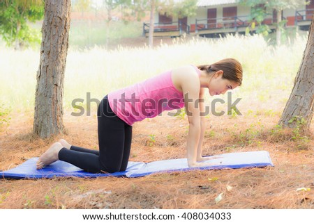 pretty brown hair girl in park and is relaxing with yoga