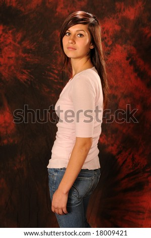 Pretty brown haired teenage girl in a pink top and jeans