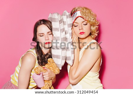 pretty brunette and curly blonde are sleeping - stock photo