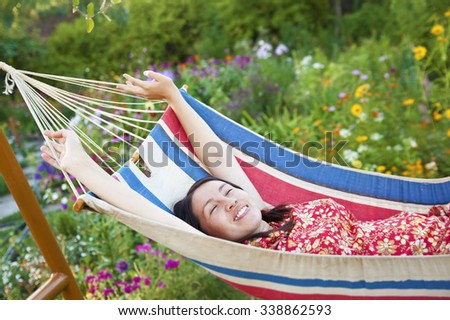 Pretty brunette asian girl relaxing in a hammock on a summer day against spring flowers in garden Young adult woman lie alone above land with green grass