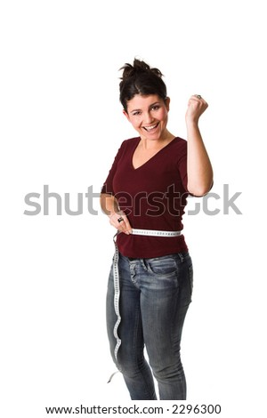 pretty brunette being very happy while holding a measuring tape around her waist showing that she lost some centimeters - stock photo