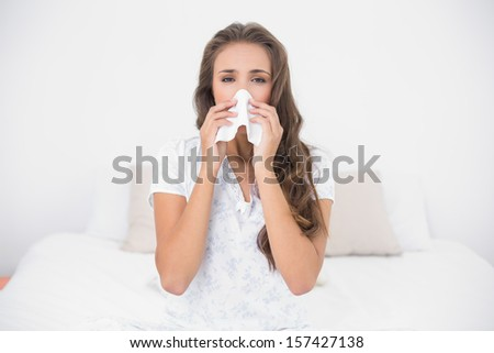 Pretty brunette blowing her nose in bright bedroom