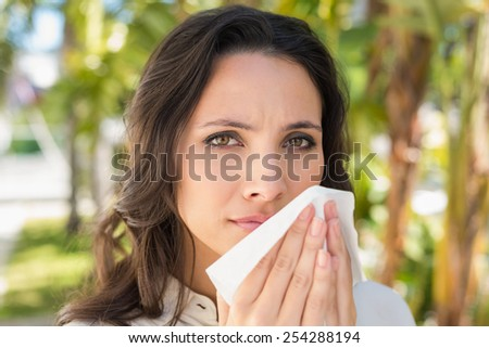 Pretty brunette blowing her nose on a sunny day - stock photo