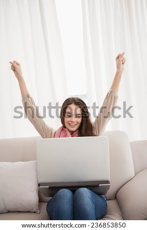 Pretty brunette cheering using laptop at home in the living room