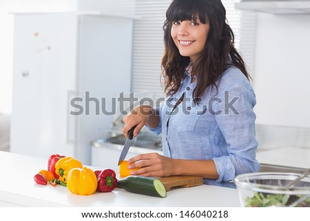 Pretty brunette chopping peppers at kitchen counter