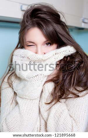Pretty brunette covering herself in a warm sweater