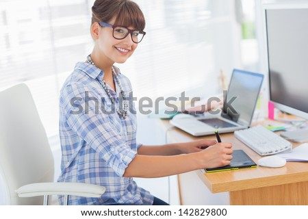Pretty brunette designer working on her graphics tablet - stock photo