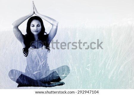 Pretty brunette doing yoga against green meadow