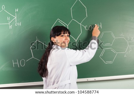Pretty brunette drawing chemical structure on a chalkboard - stock photo