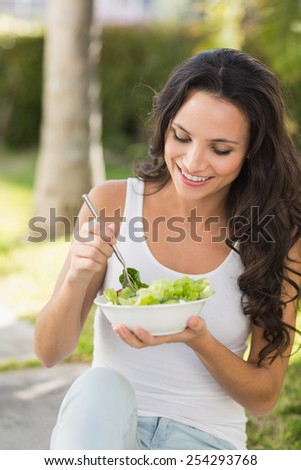 Pretty brunette eating bowl of salad on a sunny day - stock photo