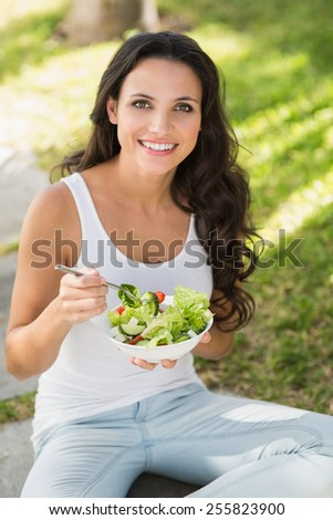 Pretty brunette eating bowl of salad on a sunny day